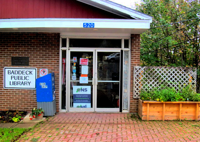 Exterior of Baddeck Library building showing Book returns bin to the left of the entrance doors and raised garden bed to the right of the entrance doors.