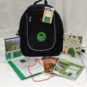 Forest Nature Backpack Kit with contents on display: Hiking Trails of Cape Breton book; Forest Nature Backpack instructions; handheld magnifying glass; community nature journal; trees of Eastern canada brochure; Walking Trails and Outdoor Spaces of CBRM brochure; Animal Signatures book; Woodland and Forest children's book.