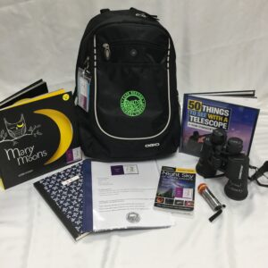 Night Sky Nature Backpack with contents on display: Many Moons children's book; community nature journal; Night Sky nature backpack instructions;  National Geographic Pocket Guide to the Night Sky of North America book; night viewing flashlight; Night Sky binoculars; 50 Things to see with a telescope young stargazer's guide book.