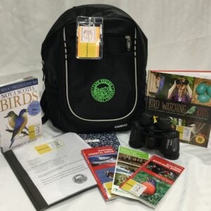 Birdwatching Backpack showing contents of the kit: Formac Field Guide to Nova Scotia Birds; Birdwatching kit instructions; community nature journal; 3 brochures: eastern coastal birds, Walking Trails and Outdoor Spaces of CBRM, and Eastern backyard birds; Binoculars; Bird Watching For Kids Book.