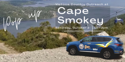 Photo taken from the top of Cape Smokey Ingonish showing Gondola and coastline in distance. Foreground shows Victoria County Outreach car superimposed onto the top of the mountain